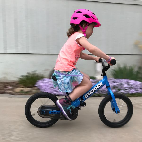 Girl focusing on her path while pedaling a blue 14x Sport
