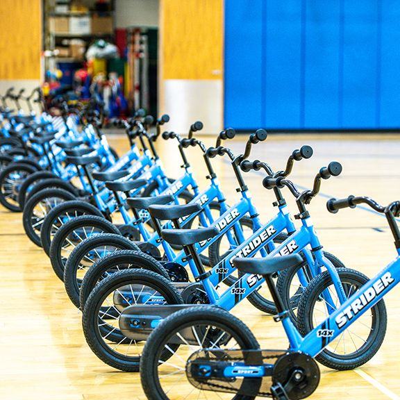 Row of blue 14x bikes lined up in gymnasium