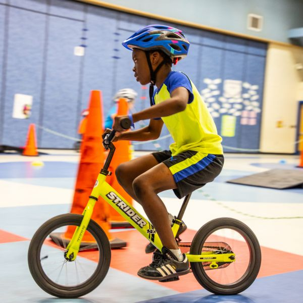 Young boy pedaling green 14x Sport around a cone in PE class