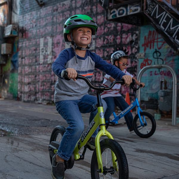 Young boy smiling while pedaling green 14x Sport