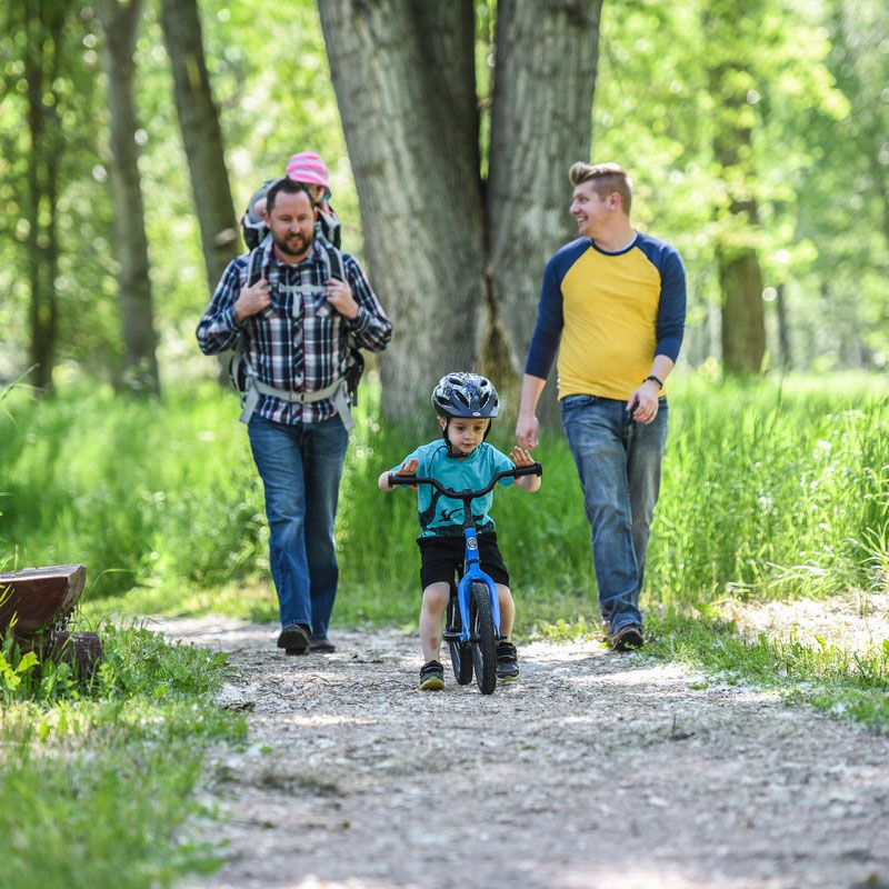 Family walking while kid rides bike