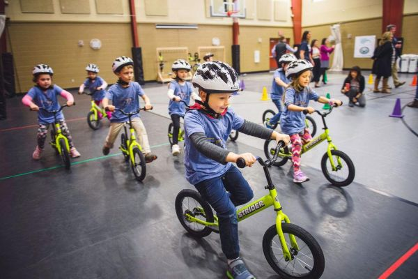 A group of schoolchildren in blue shirts and white helmets practice striding on yellow Strider 14x balance bikes